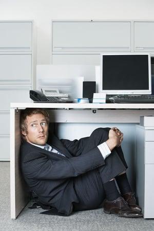 business-man-hiding-under-desk.jpg
